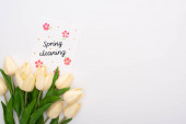 top view of spring tulips near spring cleaning card on white background