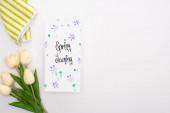 vrchní pohled na jarní tulipány a ručník v blízkosti karty jarní úklid na bílém pozadí