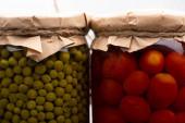 Nahaufnahme von hausgemachten leckeren Dosentomaten und grünen Erbsen in Gläsern