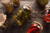 Blick von oben auf hausgemachte leckere Essiggurken in Gläsern auf Holztisch