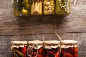horní pohled na zelené a červené chutné domácí okurky ve sklenicích na dřevěném rustikálním stole