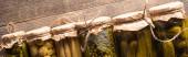 Blick von oben auf grüne, schmackhafte hausgemachte Essiggurken in Gläsern auf rustikalem Holztisch, Panoramaaufnahme