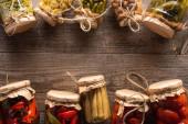 vrchní pohled na domácí chutné okurky ve sklenicích na dřevěném stole s kopírovacím prostorem