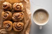 vrchní pohled na čerstvé domácí skořicové role na pergamenovém papíru na mramorovém povrchu s kávou