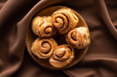 top view of fresh homemade cinnamon rolls on plate on silk brown cloth