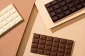 vrchní pohled na lahodné bílé, mléko a tmavé čokoládové tyčinky na béžovém pozadí