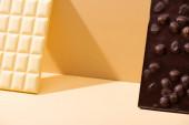 lahodné rozbité bílé a tmavé čokoládové tyčinky s ořechy na béžovém pozadí