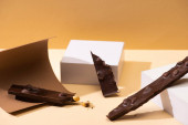 vynikající tmavá čokoláda s kousky ořechů, papír a kostky na béžovém pozadí