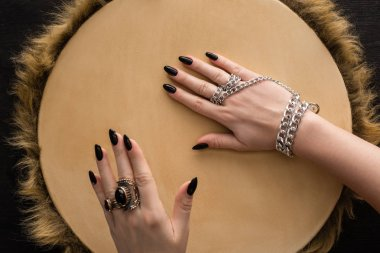 Top view of shaman with jewelry rings and chain on hands playing on tambourine isolated on black