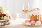selektivní zaměření lahodného velikonočního dortu zdobeného sněhovou pusinkou s růžovými a bílými vejci na talíři u sklenice na víno a květin