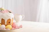výborný velikonoční dort zdobený sněhovou pusinkou v blízkosti barevných vajec na talíři