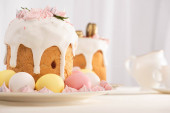 selective focus of delicious Easter cakes decorated with meringue near colorful eggs on plates