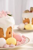 szelektív fókusz ízletes húsvéti sütemények habcsók és színes tojás tányérokon