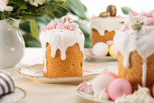 selective focus of Easter cakes with white glaze and meringue on table