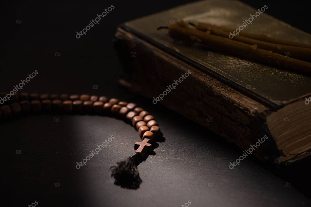 Selective focus of holy bible with candles and rosary with cross in dark with sunlight stock vector