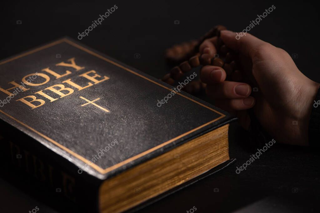 Cropped view of woman holding rosary near holy bible in dark with sunlight stock vector
