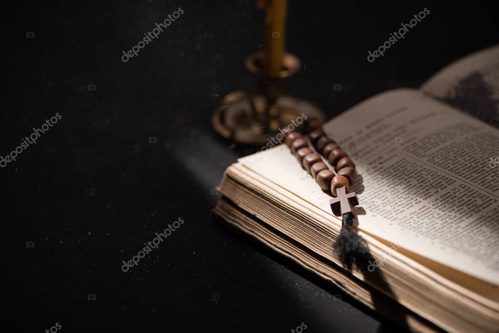 KYIV, UKRAINE - JANUARY 17, 2020: selective focus of candlestick near bible with catholic rosary in dark with sunlight stock vector