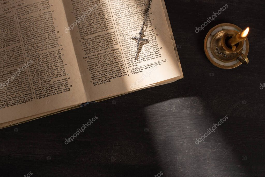 KYIV, UKRAINE - JANUARY 17, 2020: top view of open holy bible with cross near candle on dark background with sunlight stock vector