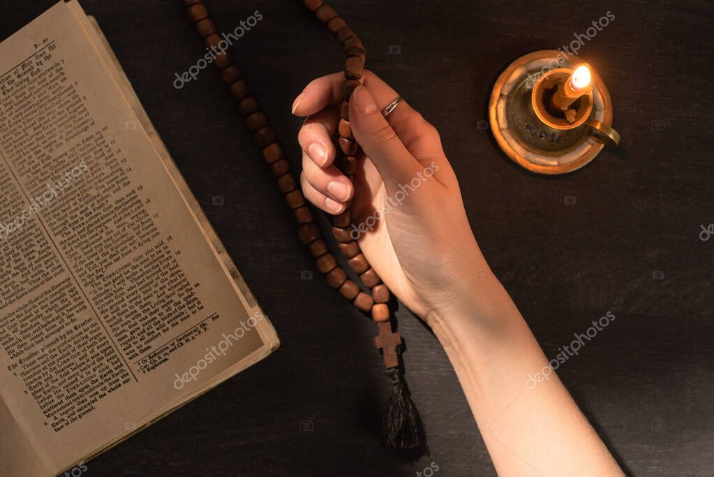 KYIV, UKRAINE - JANUARY 17, 2020: cropped view of woman praying with rosary near open holy bible and candle stock vector