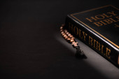 Photo holy bible with rosary on black dark background