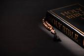 szent biblia rózsafüzérrel fekete sötét háttér