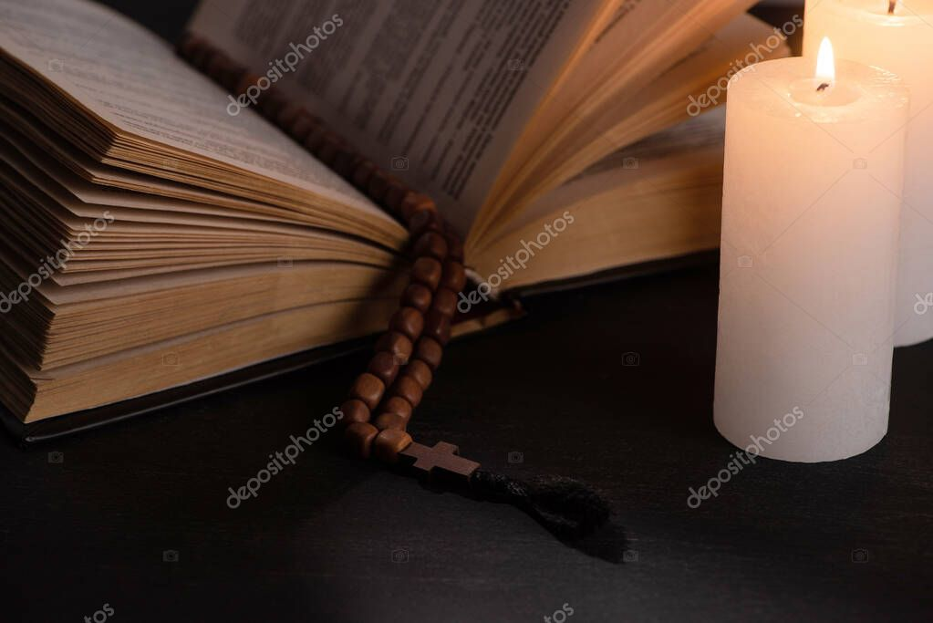Holy bible with rosary on black dark background with burning candles stock vector