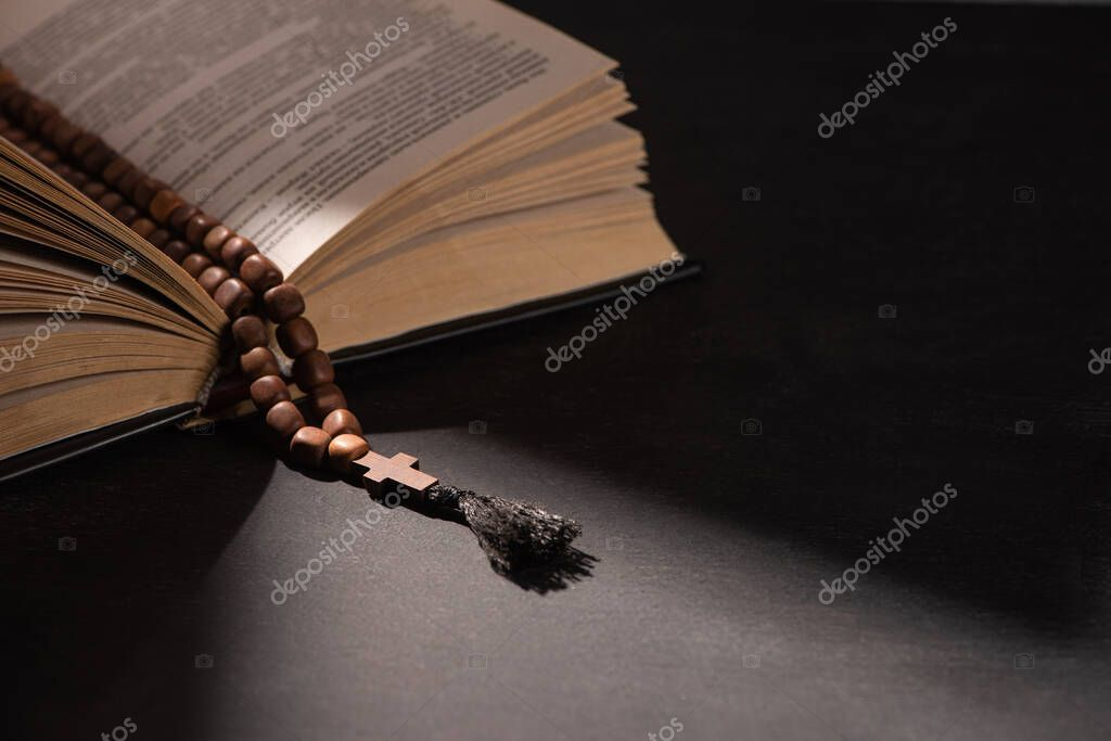Holy bible with rosary on black dark background with sunlight stock vector