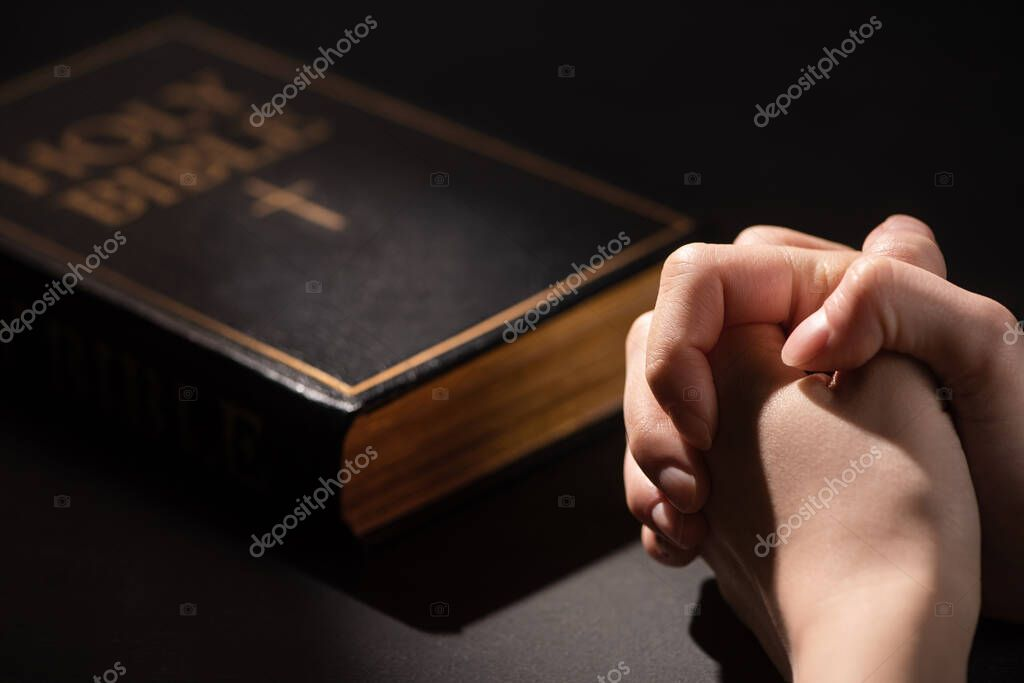 Cropped view of woman praying near holy bible in dark stock vector