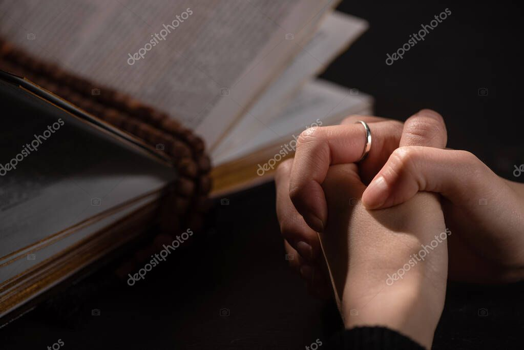 Cropped view of woman praying near holy bible with rosary in dark stock vector