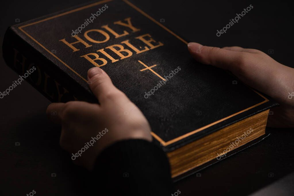 Cropped view of woman holding holy bible in dark stock vector