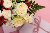 zblízka pohled na kytice květin ve slavnostní dárkové krabici s lukem na růžovém pozadí