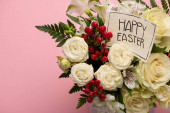 bouquet of flowers in festive gift box with happy Easter greeting card on pink background
