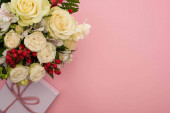 vrchní pohled na kytice květin ve slavnostní dárkové krabici s lukem na růžovém pozadí