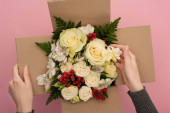 partial view of woman touching bouquet of flowers in cardboard box on pink background