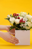 cropped view of woman holding spring fresh bouquet of flowers in box on yellow background