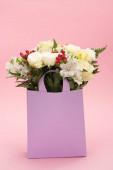 Fényképek bouquet of flowers in violet paper bag on pink background