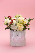 Photo bouquet of flowers in festive gift box with bow on pink background