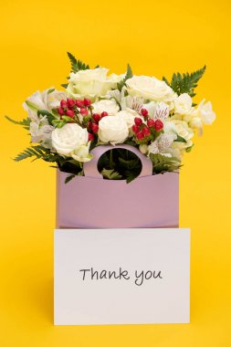 Spring fresh bouquet of flowers in violet paper bag near thank you card isolated on yellow stock vector