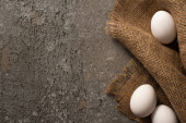 top view of white chicken eggs on sackcloth on grey textured background