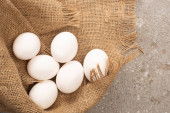 Photo top view of white chicken eggs on sackcloth on grey concrete background