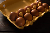 Fotografie brown chicken eggs in egg tray on brown wooden background