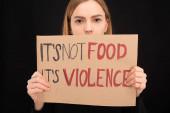 žena s obskurním obličejem drží lepenkový nápis s jeho ne jídlo jeho nápis násilí izolované na černé
