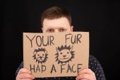 muž s obskurní tváří držící kartónovou ceduli s vaší kožešinou měl obličejový nápis izolovaný na černé
