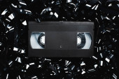 Fotografie Draufsicht auf schwarze VHS-Kassette auf Filmstreifen