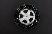 Fotografie Draufsicht auf schwarzen Filmstreifen und Filmrolle in rostigem Blechetui isoliert auf schwarz