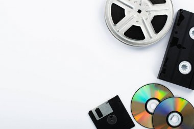 Top view of CD discs, black VHS cassette, diskette and film reel on white background stock vector