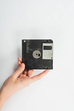 partial view of man holding black diskette on white background