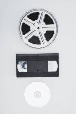 Top view of film reel, VHS cassette and CD disc on white background stock vector