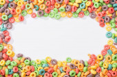 Fotografie top view of bright multicolored breakfast cereal arranged in frame on white background