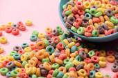 jasné barevné snídaně cereálie rozptýlené z mísy na růžovém pozadí